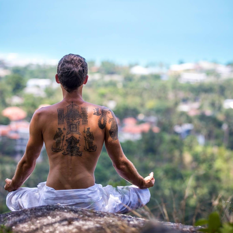 A man is pictured meditating in Vikasa Yoga Samui