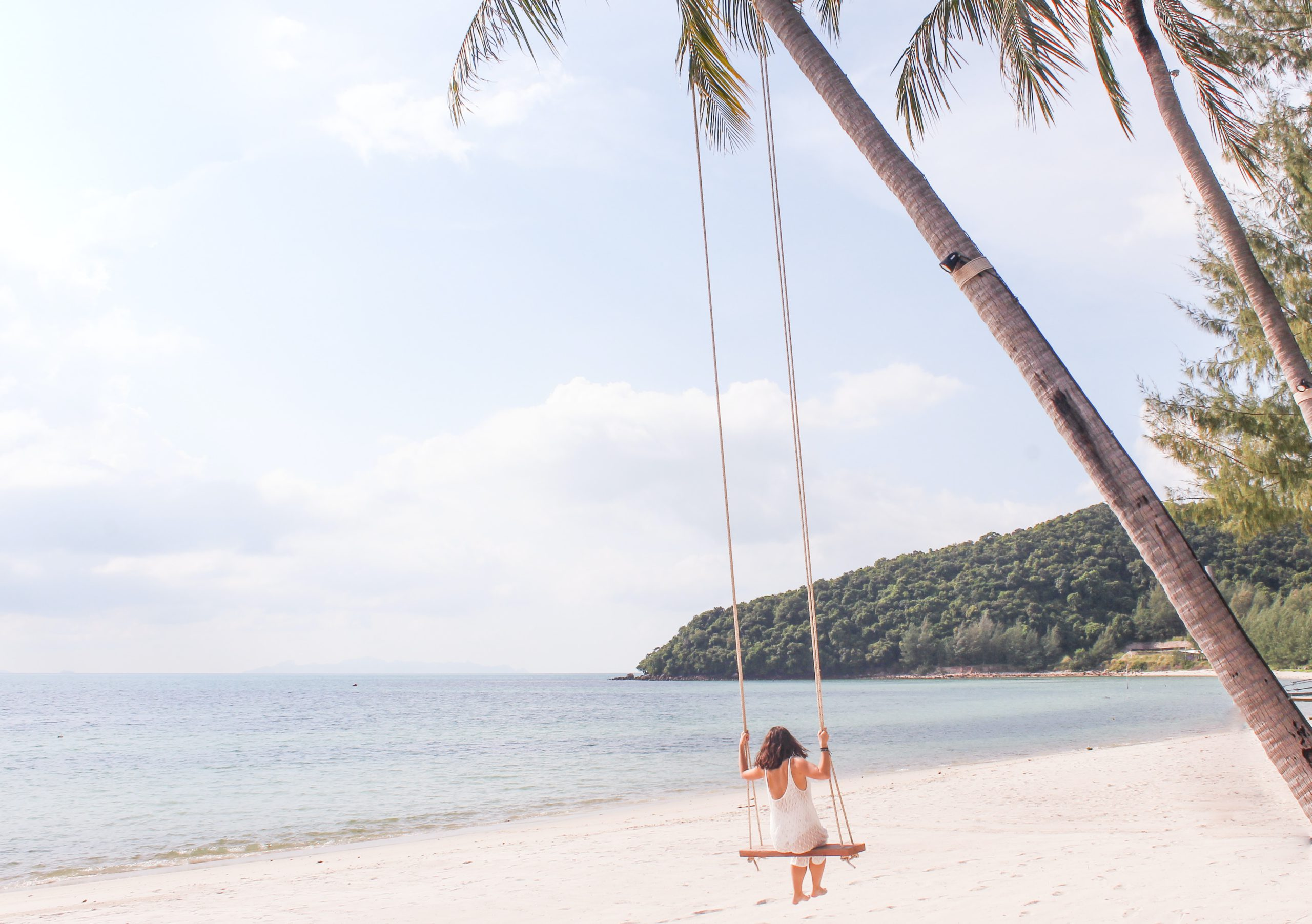 Photo of a girl on a rope swing, by the beach